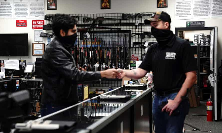 A customer hands over his ID for a background check to a manager before making a purchase at Firearms Unknown in Oceanside, California.