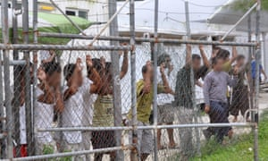 Asylum seekers stand behind a fence in Oscar compound at the Manus Island detention centre in Papua New Guinea, Friday, March 21, 2014.