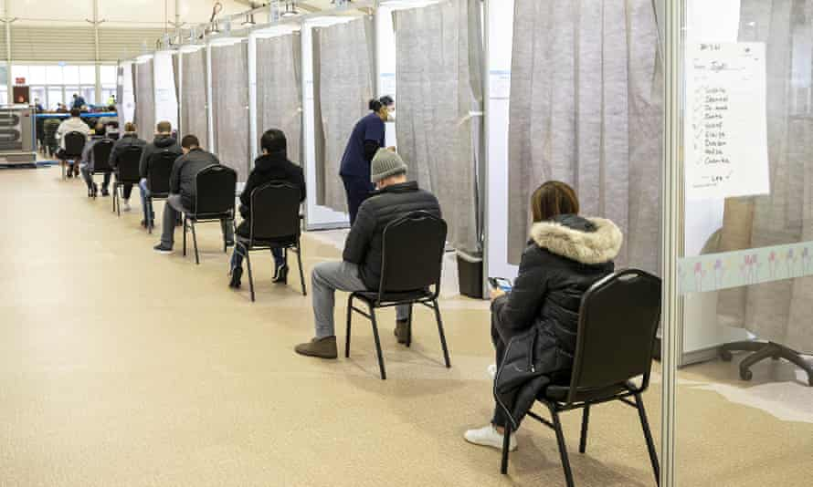 People wait to be called into a cubicle to receive a Covid-10 vaccine at the Melbourne Showgrounds vaccination centre