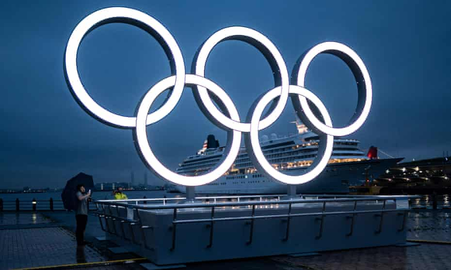 A man stands next to the Olympic rings at dusk in Yokohama