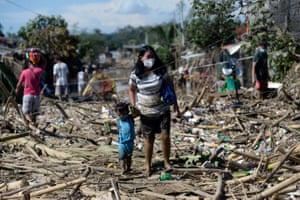 Rodriguez, Philippines A woman and a child walk on debris brought by the flood following typhoon Vamco, in Rizal province