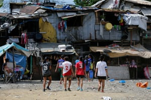 Members of the Philippines team walk through a slum area to their dormitory, after a training session in Payatas, Quezon City, north of Manila