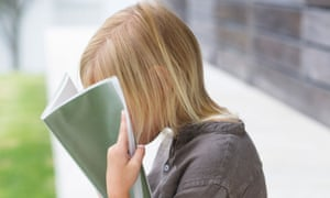 Girl holding a book in front of her face
