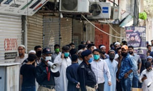 A police officer uses a megaphone to disperse shopkeepers, who gather to reopen their shops at a closed electronics market in Karachi, Pakistan.