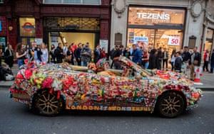 A man drives an elaborately decorated Saab through Oxford Circus, London, UK