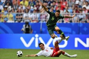 Australia's defender Joshua Risdon (top) hurdles Denmark's midfielder Thomas Delaney