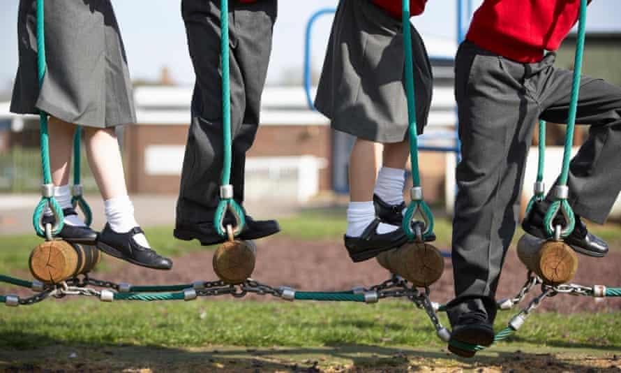 Children in school uniform on climbing equipment.