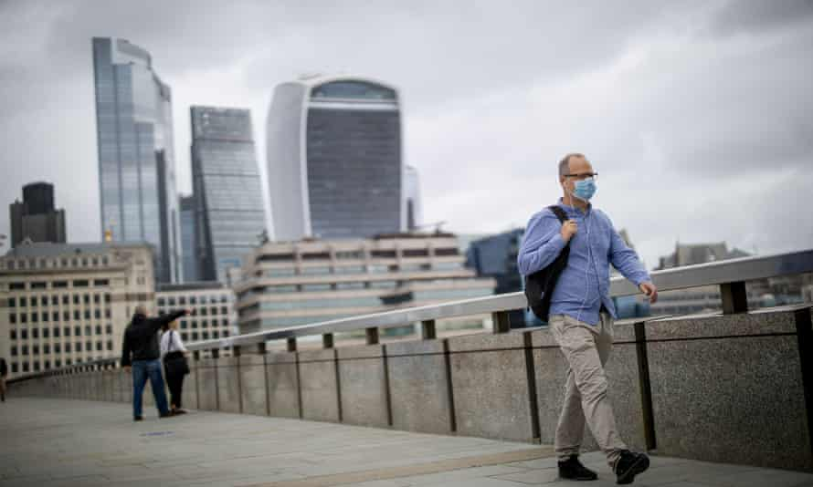 A man in a face mask walks over London Bridge with City of London offices in the background