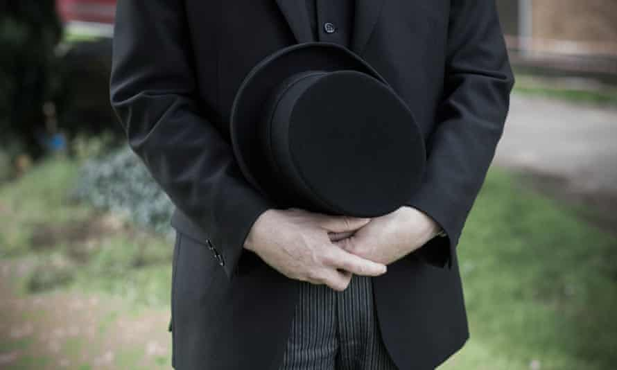 a funeral director holding a hat
