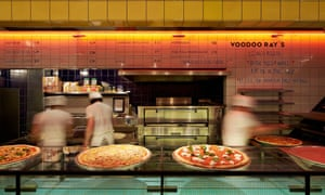 View across counter towards pizza oven with pizza bakers at Voodoo Ray's, Dalston, London.