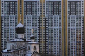 A church is dwarfed by high-rise apartment buildings in St Petersburg, Russia