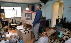 a man lugs packed boxes to a van