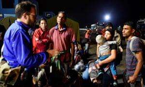 An UNHCR official speaks with Venezuelan migrants upon their arrival in Ecuador.