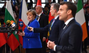 The German chancellor, Angela Merkel, looking at the French president, Emmanuel Macron, as they both conduct media interviews on arrival at the summit.