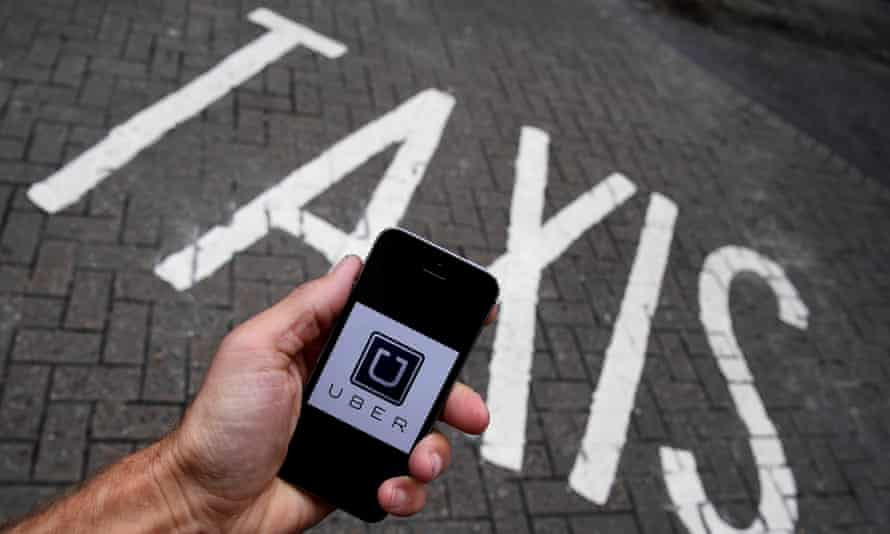 A man holding a mobile phone displaying the Uber logo