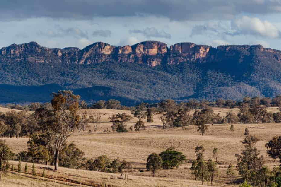 Grassy plains backed by natural bush and rugged sandstone ridges within the Capertee Valley, on the western foothills of the Blue Mountains.