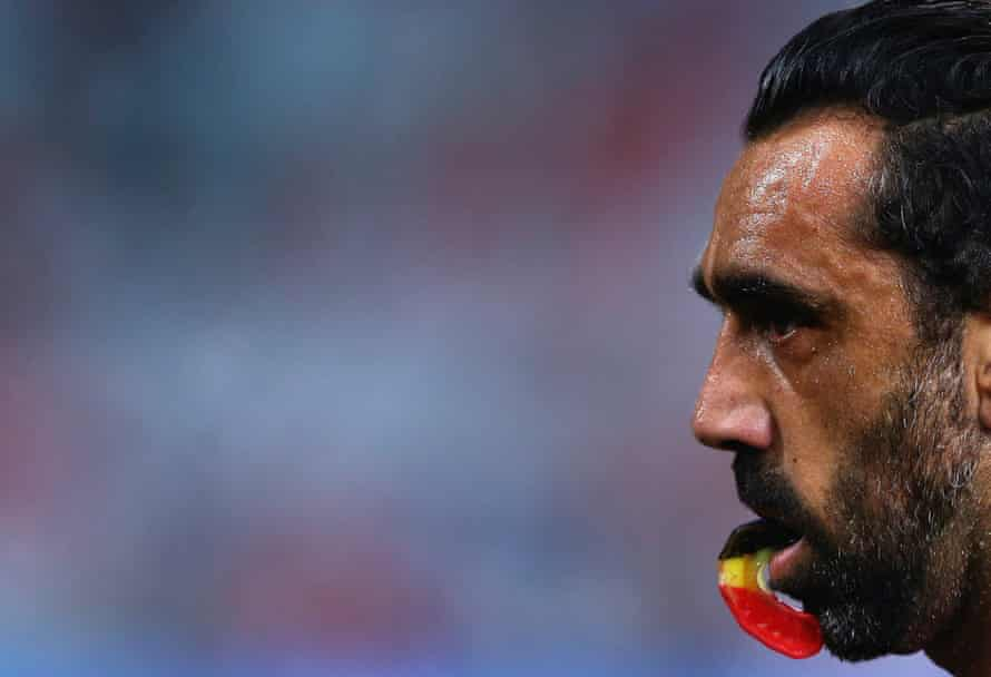 a close up of Adam Goodes holding onto a red, yellow and black mouth guard with his teeth