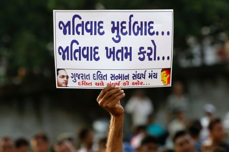 A man holds a placard that reads 'Down with racism, finish racism', during a rally protesting about atrocities against Dalits, in Ahmadabad, India