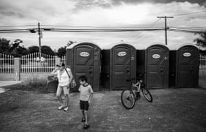 Juana Garcia and her son Christopher Castro use the portable bathrooms at the Emmanuel Church. They have no running water and depend on the church facilities to stay clean.