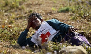 A wounded Red Cross volunteer lies on ground after a rescue convoy was attacked by Kokang rebels near self-administered Kokang capital Laukkai, northern Shan State, Burma. The government has declared a state of emergency in the region.