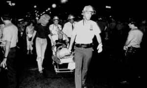 A man being taken away on a stretcher after the Tompkins Square Park riots in 1988
