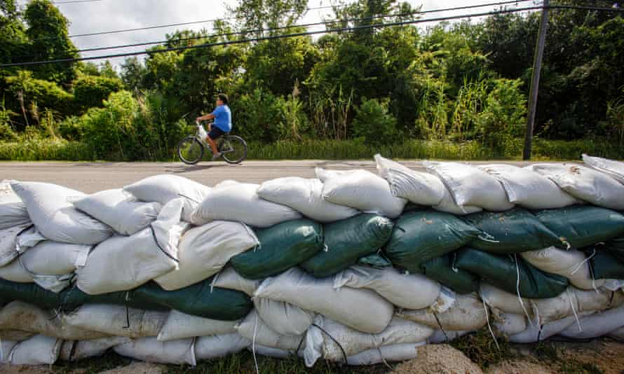 A young child rides his bike by a line of sand bags in Jean Lafitte, Louisiana Monday.
