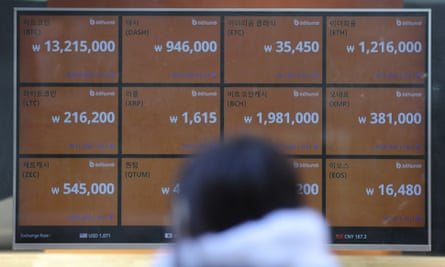 A woman walks by a screen showing prices, including bitcoin, top left, in downtown Seoul, South Korea.