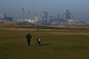 A man plays golf in front of a closed-down steelworks plant in Redcar