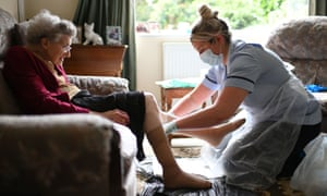 File photo  of a nurse, wearing personal protective equipment (PPE), changing the dressings on the legs of an elderly woman during a home visit.