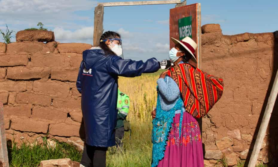 A government worker checks the temperature of a Quechua Indigenous voter in the village of Capachica, in Puno, Peru.