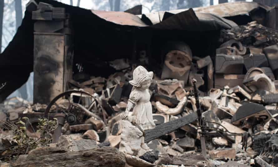 A statue stands before a collapsed shed in Paradise.