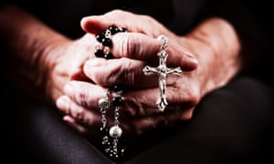 Elderly hands clasp a rosary.