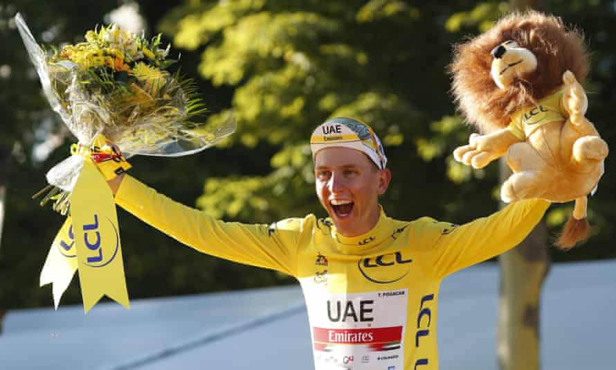 Tadej Pogacar celebrates on the podium after being confirmed as the general classification winner of this year's Tour de France.