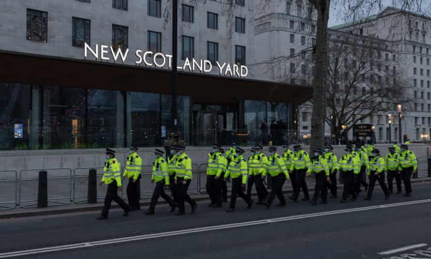 Officers march past New Scotland Yard in London following a protest against the handling of a vigil held for Sarah Everard on Clapham Common.