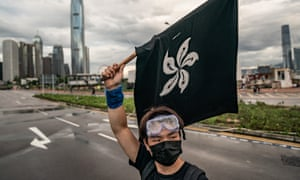 An anti-extradition protester waves a black Hong Kong flag on a street outside the Legislative Council Complex.