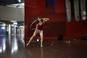 Stav Pinto, 24, uses a hula hoop as she practices her acrobatics skills during a weekly informal circus community meeting at the central bus station in Tel Aviv, Israel.