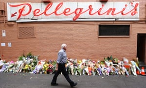 A man walks past floral tributes outside of Pellegrini's
