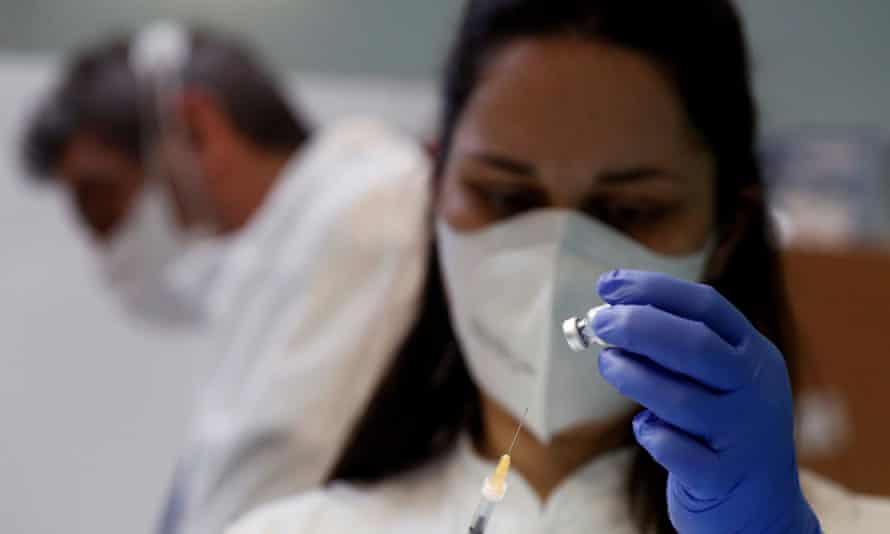 healthcare worker draws the vaccine from a vial through a syringe