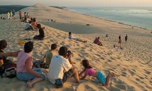Turistas en la duna du Pyla en la puesta del sol, Arcachon, Francia