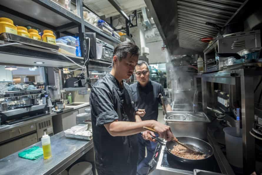 A chef makes spaghetti bolognese with plant-based OmniPork as David Yeung, the co-founder and co-chief executive officer of Green Monday, looks on at the Kind Kitchen restaurant in Hong Kong.