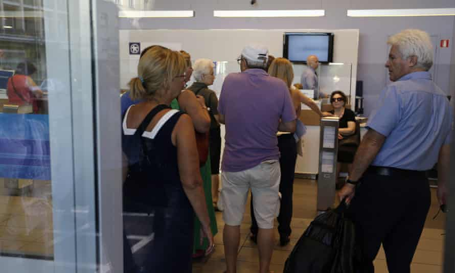 Customers wait to be served inside an Alpha Bank branch in Athens this morning.