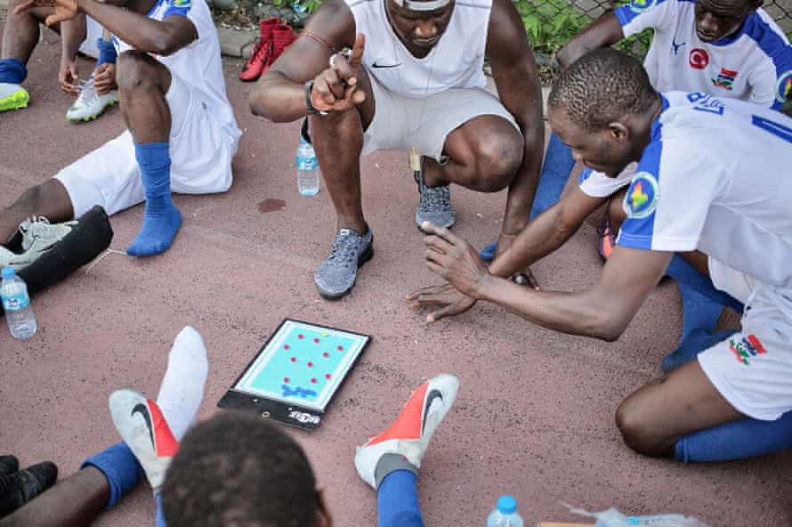 The coach of the Gambia team explains some tactics during the halftime
