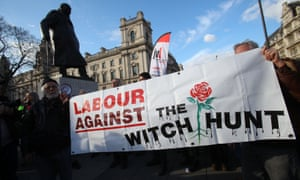 Labour supporters hold a banner as people protest against antisemitism in the Labour party in Parliament Square.