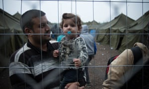 A Syrian refugee carrying his child in a camp near the Hungary-Serbia border where they are being fingerprint registered.