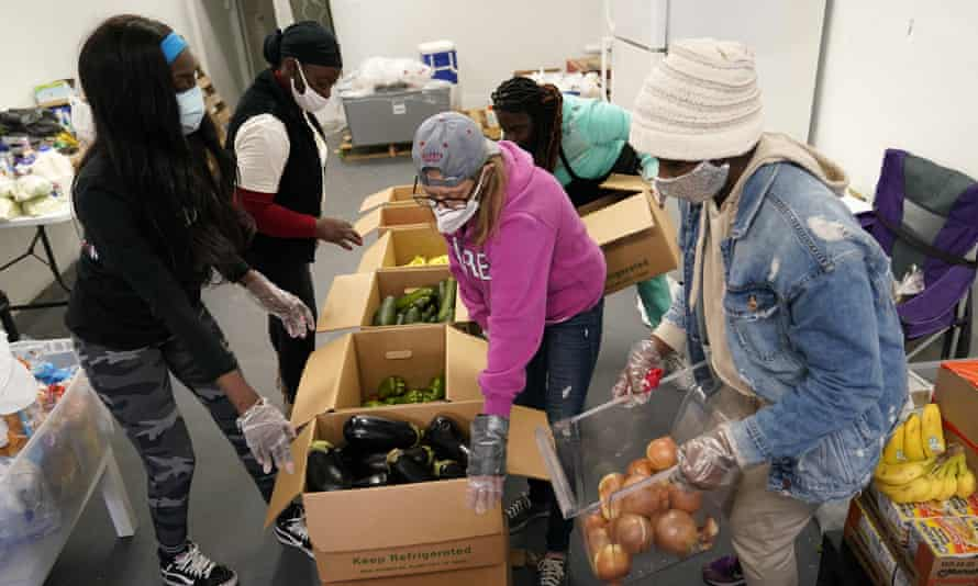 Sherina Jones, left, works with volunteers organizing food for distribution in December in the Liberty City neighborhood of Miami.