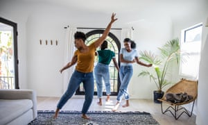 Women friends dancing in the living room of an apartment