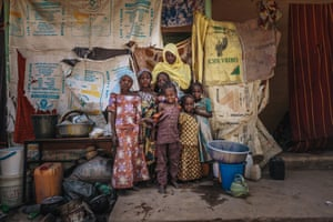 Atai and her children pose in front of their make-shift shelter in the one of the IDP camps in Maiduguri, Nigeria