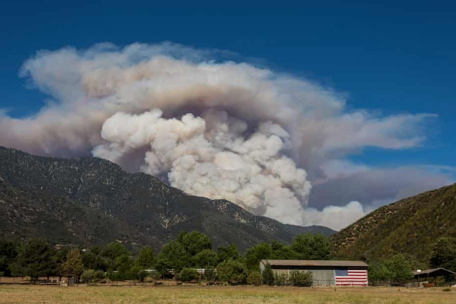 Smoke from the Apple fire rises behind a farm in Cherry Valley, California.