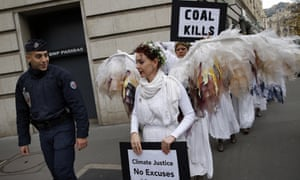 Protesters walk past a gendarme outside the talks in Paris.