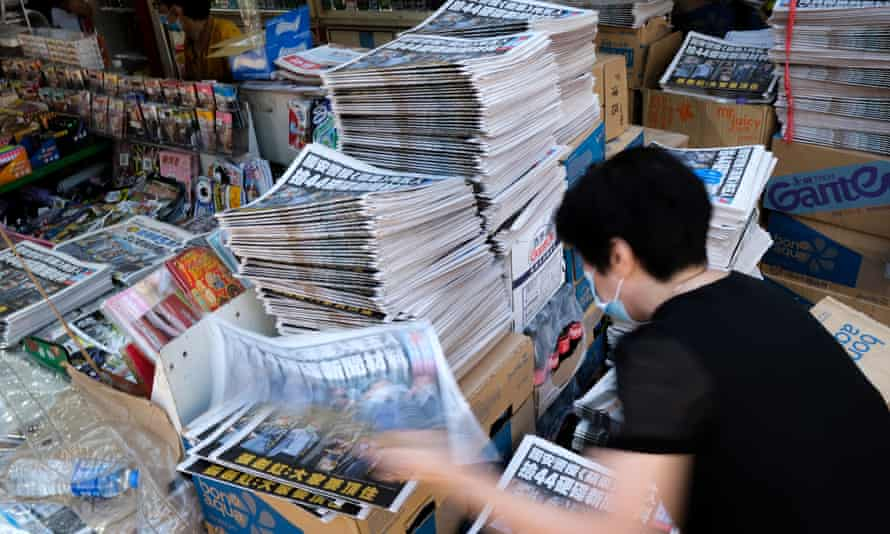 Employees at the newspaper stall sort out the newspapers of Apple Daily in Hong Kong